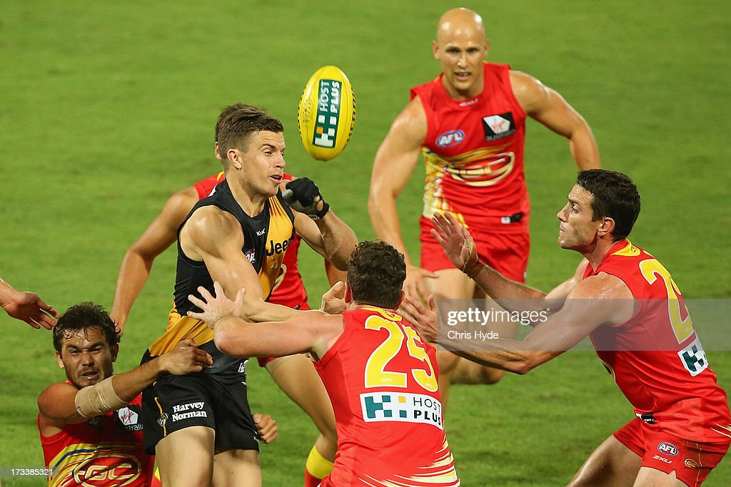 <a gi-track='captionPersonalityLinkClicked' href=/galleries/search?phrase=Brett+Deledio&family=editorial&specificpeople=524933 ng-click='$event.stopPropagation()'>Brett Deledio</a> of the Tigers handballs during the round 16 AFL match between the Richmond Tigers and the Gold Coast Suns at Cazaly's Stadium on July 13, 2013 in Cairns, Australia.