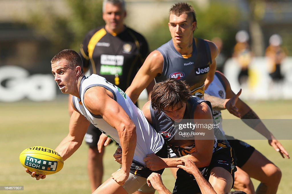 <a gi-track='captionPersonalityLinkClicked' href=/galleries/search?phrase=Brett+Deledio&family=editorial&specificpeople=524933 ng-click='$event.stopPropagation()'>Brett Deledio</a> of the Tigers handballs whilst being tackled during a Richmond Tigers AFL training session at ME Bank Centre on March 26, 2013 in Melbourne, Australia.