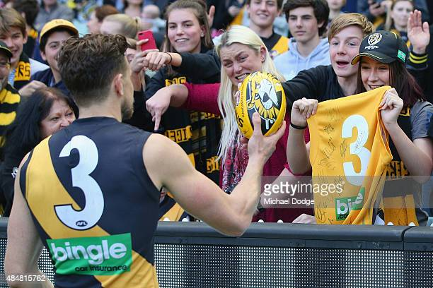 Brett Deledio of the Tigers hands a ball over to a fan after their win during the round 21 AFL match between the Collingwood Magpies and the Richmond...