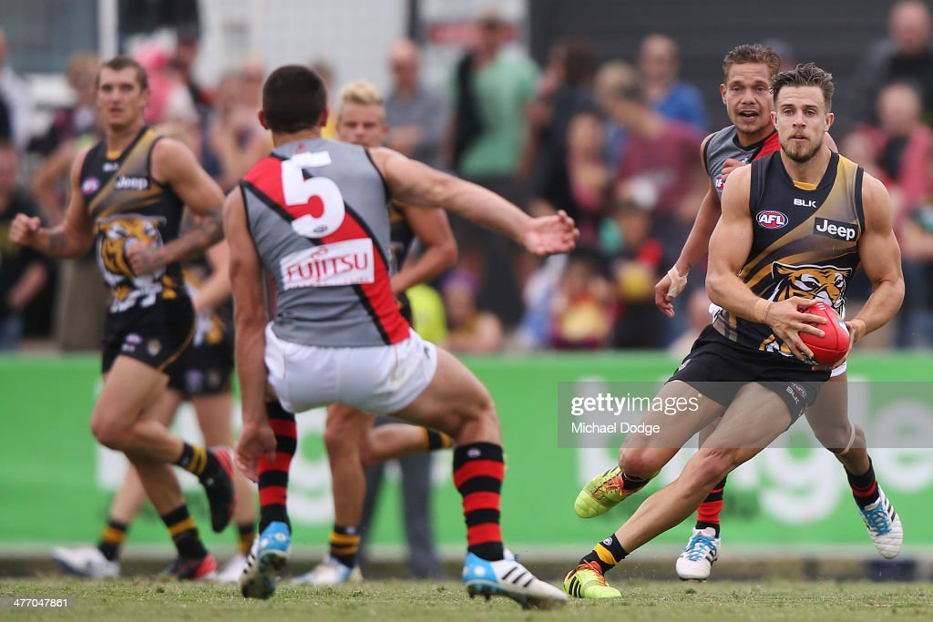 Brett Deledio of the Tigers runs with the ball past Brenton Stanton of the Bombers during an AFL Practice Match between the Richmond Tigers and the Essendon Bombers at Punt Road Oval on March 7, 2014 in Melbourne, Australia.