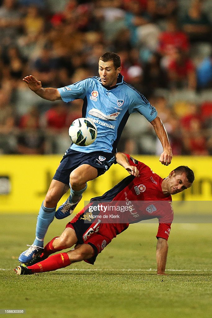 <a gi-track='captionPersonalityLinkClicked' href=/galleries/search?phrase=Brett+Emerton&family=editorial&specificpeople=206493 ng-click='$event.stopPropagation()'>Brett Emerton</a> of Sydney is tackled by Cameron Watson of Adelaide during the round 14 A-League match between Adelaide United and Sydney FC at Hindmarsh Stadium on December 31, 2012 in Adelaide, Australia.