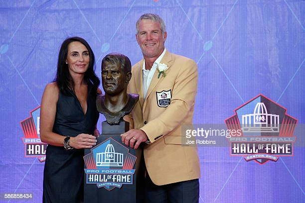 Brett Favre former NFL quarterback and his wife Deanna pose with his bronze bust during the NFL Hall of Fame Enshrinement Ceremony at the Tom Benson...