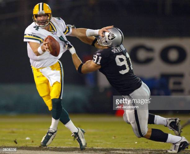 Brett Favre of the Green Bay Packers avoids a sack attempt by Tyler Brayton of the Oakland Raiders during an NFL game on December 22 2003 at the...