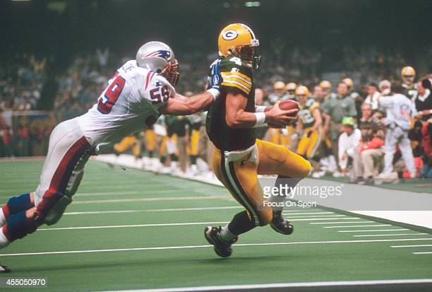 Brett Favre of the Green Bay Packers gets pushed down at the goal line by Todd Collins of the New England Patriots during Super Bowl XXXI January 26...