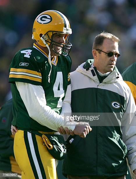 Brett Favre of the Green Bay Packers is lead off the field by a team doctor after injuring his arm on a sack by the New England Patriots on November...