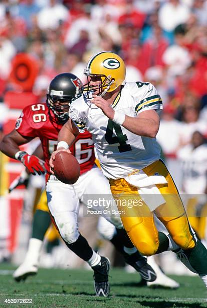 Brett Favre of the Green Bay Packers scrambles away from the pressure of Hardy Nickerson of the Tampa Bay Buccaneers during an NFL football game at...