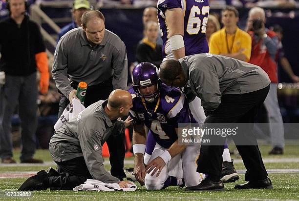 Brett Favre of the Minnesota Vikings is assisted by medical staff against the Buffalo Bills defense at the Mall of America Field at the Hubert H...