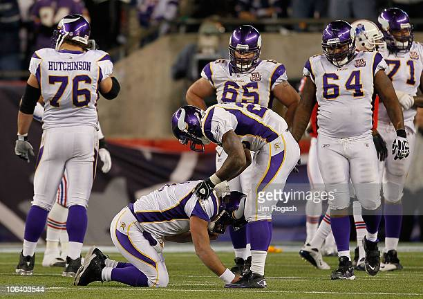 Brett Favre of the Minnesota Vikings is attended to by teammate Adrian Peterson after being injured in the fourth quarter against the New England...
