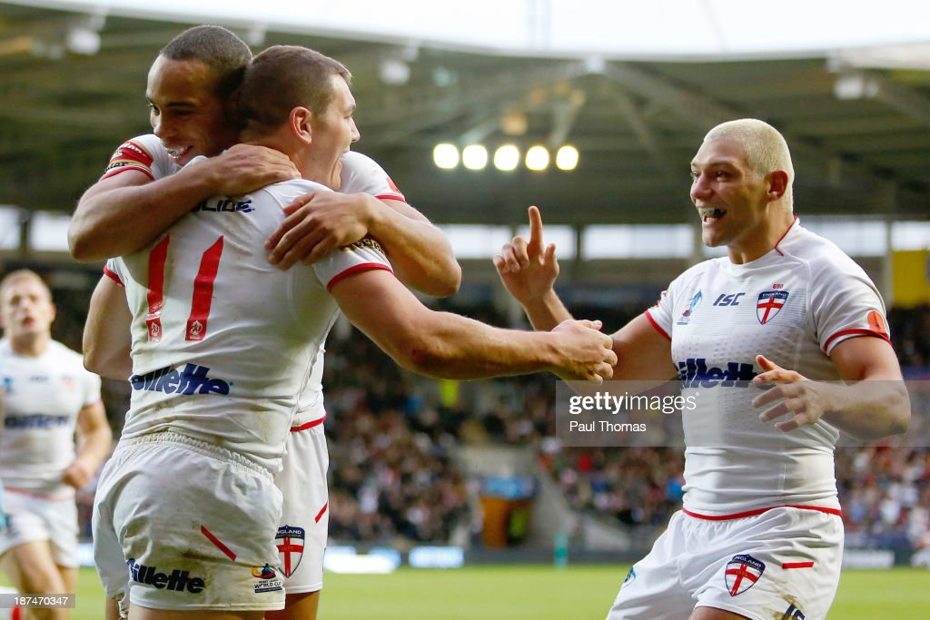 Brett Ferres of England celebrates his try with team mates Leroy Cudjoe and Ryan Hall during the Rugby League World Cup Group A match at the KC...