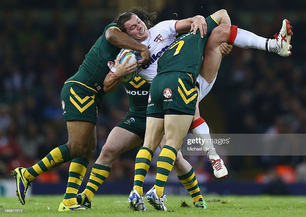 Brett Ferres of England is upended by Cooper Cronk and Sam Thaiday of Australia during the Rugby League World Cup Group A match between Australia and England at the Millennium Stadium on October 26, 2013 in Cardiff, Wales.