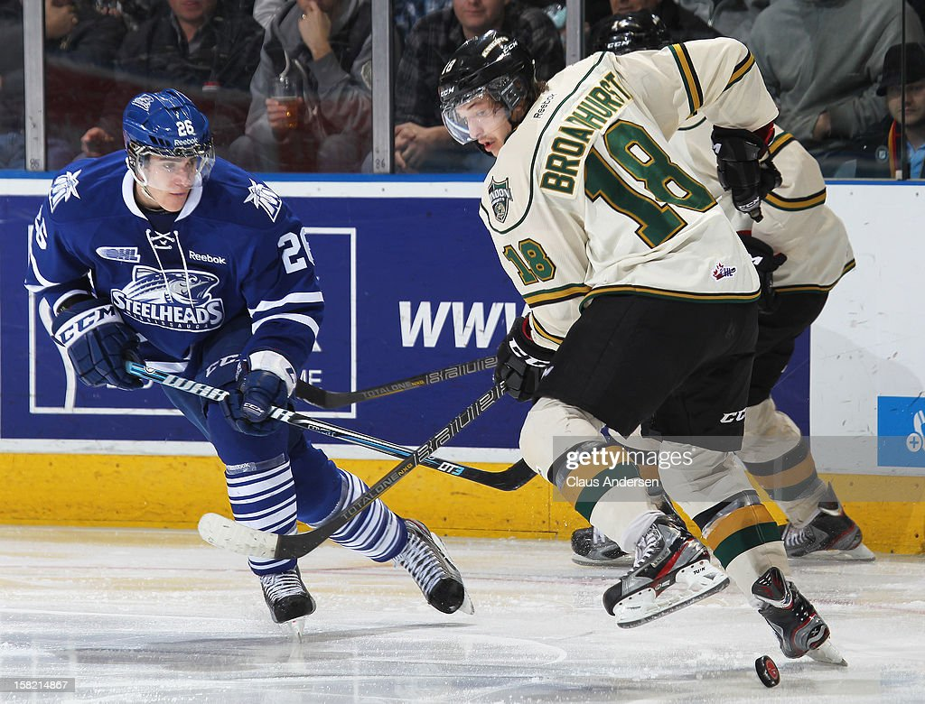 Brett Foy #26 of the Mississauga Steelheads looks to grab a loose puck between the legs of Alex Broadhurst #18 of the London Knights in an OHL game on December 9, 2012 at the Budweiser Gardens in London, Ontario, Canada. The Knights defeated the Steelheads 5-2 and tied their franchise record of 18 straight wins.