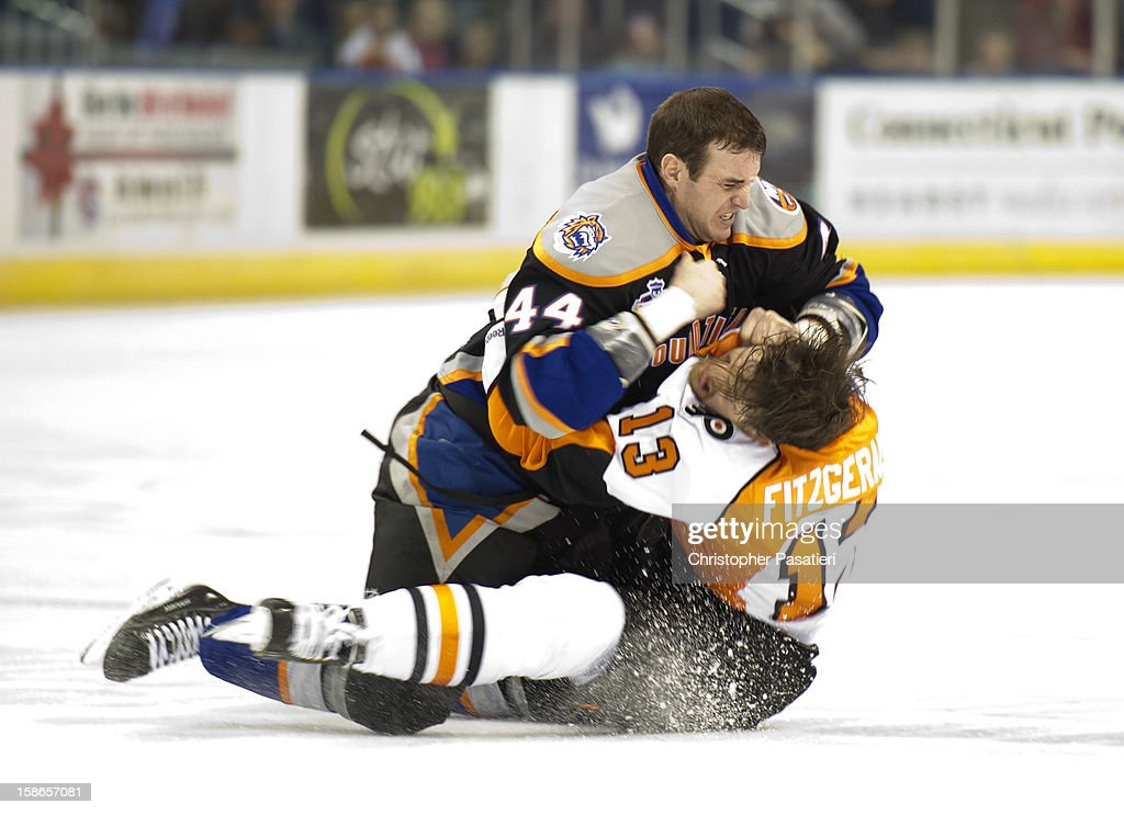 Brett Gallant #44 of the Bridgeport Sound Tigers and Zack FitzGerald #13 of the Adirondack Phantoms fight during an American Hockey League game on December 22, 2012 at the Webster Bank Arena at Harbor Yard in Bridgeport, Connecticut.