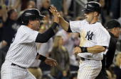 Brett Gardner and Francisco Cervelli of the New York Yankees celebrate after scoring in the seventh inning against the Chicago White Sox after a...