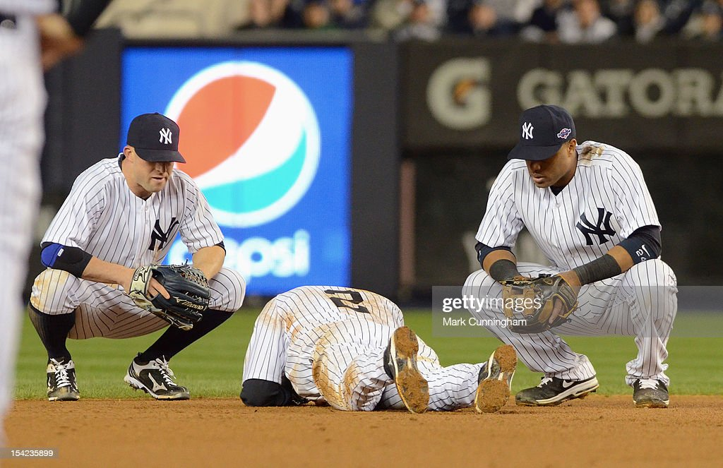 Brett Gardner #11 (L) and Robinson Cano #24 of the New York Yankees look on as Derek Jeter #2 lays on the ground after fracturing his left ankle in the top of the 12th inning against the Detroit Tigers during Game One of the American League Championship Series at Yankee Stadium on October 13, 2012 in the Bronx borough of New York City, New York. The Tigers defeated the Yankees 6-4 in 12 innings.