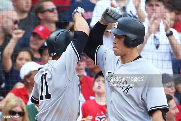 Brett Gardner high fives Aaron Judge of the New York Yankees after hitting a solo home run in the fifth inning of a game against the Boston Red Sox...
