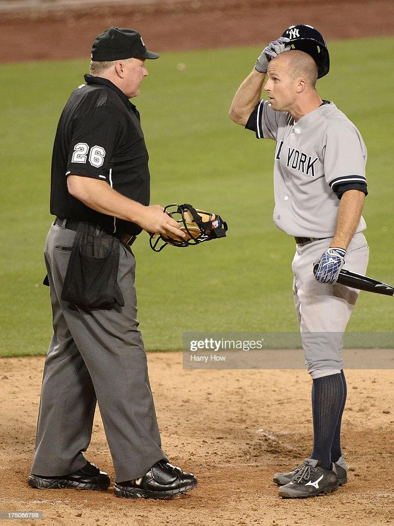Brett Gardner #11 of the New York Yankees argues his strikeout looking with home plate umpire Bill Miller to end the fifth inning at Dodger Stadium on July 30, 2013 in Los Angeles, California.