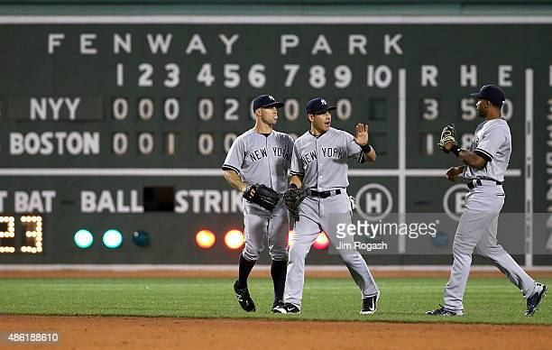 Brett Gardner of the New York Yankees celebrates 31 win over the Boston Red Sox with Jacoby Ellsbury and Chris Young at Fenway Park on September 1...