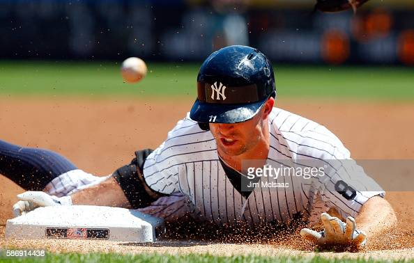 Brett Gardner of the New York Yankees dives safely into third base for a first inning triple against the Cleveland Indians at Yankee Stadium on...
