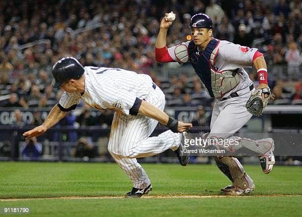 Brett Gardner of the New York Yankees gets caught in a run down between third base and home by Victor Martinez of the Boston Red Sox during the game...