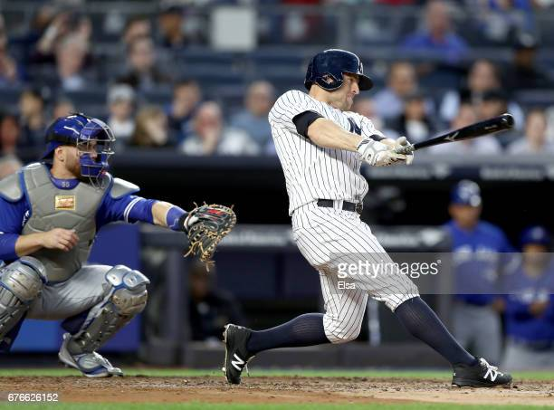 Brett Gardner of the New York Yankees hits a two run home run in the second inning as Russell Martin of the Toronto Blue Jays defends on May 2 2017...
