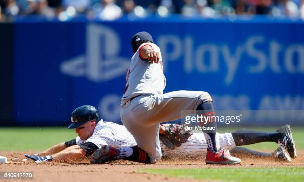 Brett Gardner of the New York Yankees is caught stealing second base during the first inning by the tag from Francisco Lindor of the Cleveland...