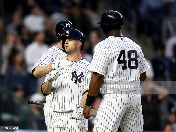 Brett Gardner of the New York Yankees is congratulated by teamamtes Chase Headley and Chris Carter of the New York Yankees after Gardner hit a two...