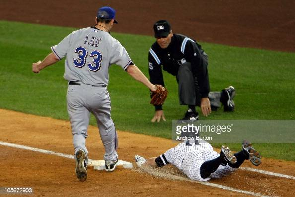 Brett Gardner of the New York Yankees is forced out at first base by pitcher Cliff Lee of the Texas Rangers in the bottom of the third inning of Game...