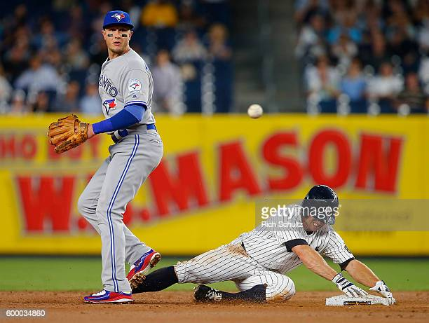 Brett Gardner of the New York Yankees is safe at second base on a single by Starlin Castro as Troy Tulowitzki of the Toronto Blue Jays watches as the...