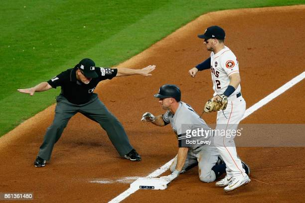 Brett Gardner of the New York Yankees is tagged out at third by Alex Bregman of the Houston Astros during game two of the American League...
