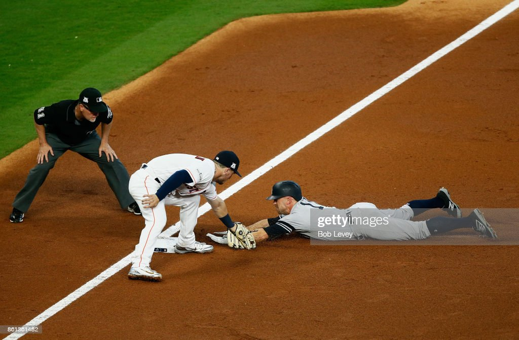 Brett Gardner #11 of the New York Yankees is tagged out at third by Alex Bregman #2 of the Houston Astros during game two of the American League Championship Series at Minute Maid Park on October 14, 2017 in Houston, Texas. The original call on the field was overturned.