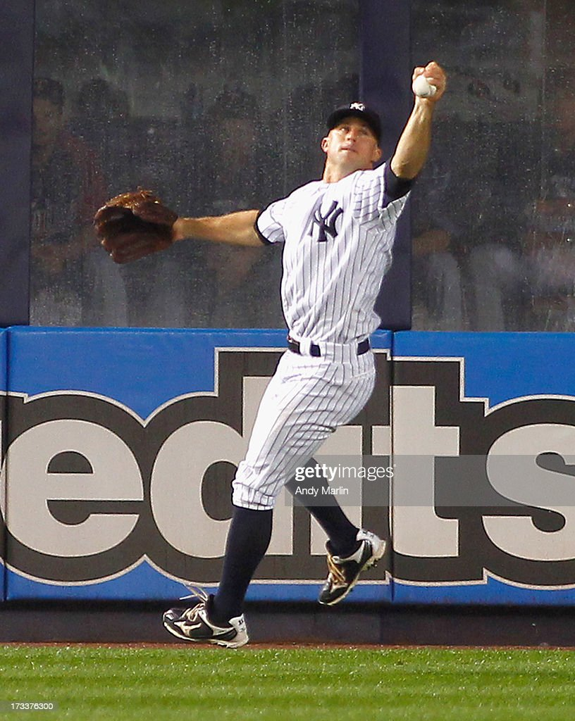<a gi-track='captionPersonalityLinkClicked' href=/galleries/search?phrase=Brett+Gardner&family=editorial&specificpeople=4172518 ng-click='$event.stopPropagation()'>Brett Gardner</a> #11 of the New York Yankees makes a barehand stab of the ball after a bad hop to hold <a gi-track='captionPersonalityLinkClicked' href=/galleries/search?phrase=Joe+Mauer&family=editorial&specificpeople=214614 ng-click='$event.stopPropagation()'>Joe Mauer</a> #7 (not pictured) of the Minnesota Twins to a double at Yankee Stadium on July 12, 2013 in the Bronx borough of New York City.