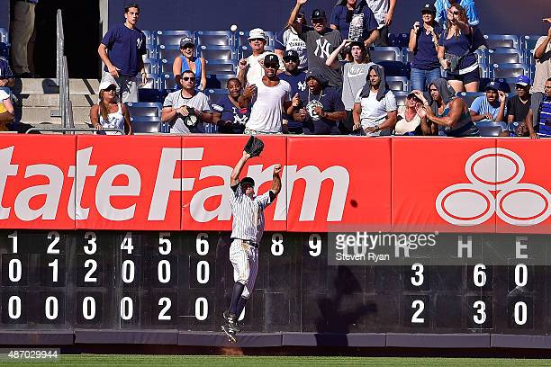 Brett Gardner of the New York Yankees makes a leaping catch at the wall in the eighth inning on a ball hit by Rene Rivera of the Tampa Bay Rays at...