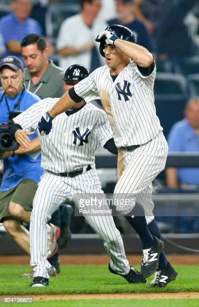 Brett Gardner of the New York Yankees runs home getting a hand shake from third base coach Joe Espada after his game winning home run in the bottom...