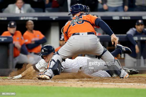 Brett Gardner of the New York Yankees slides in safely at home plate to score on a double by Aaron Judge against Brian McCann of the Houston Astros...