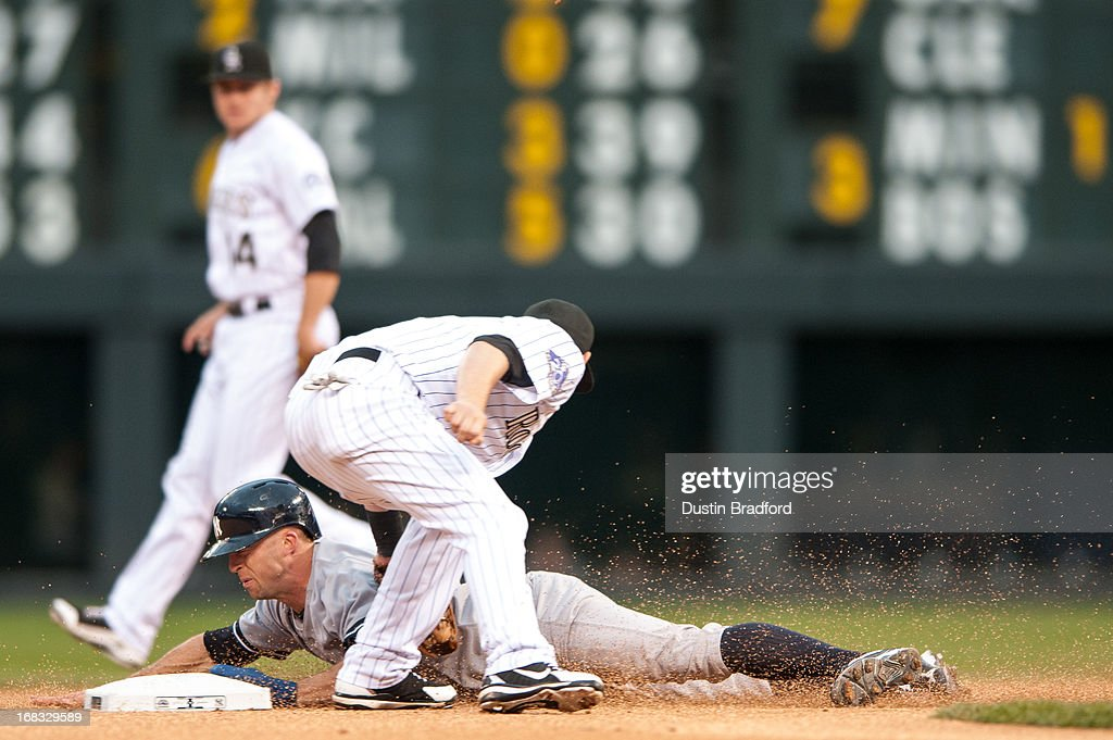 Brett Gardner #11 of the New York Yankees slides safely into second base with a steal as Reid Brignac #16 of the Colorado Rockies applies a late tag in the first inning of a game at Coors Field on May 8, 2013 in Denver, Colorado. The Yankess led the Rockies 2-0 after one inning.