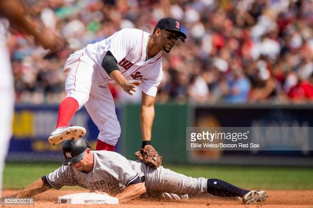 Brett Gardner of the New York Yankees steals second base as he evades the tag of Xander Bogaerts of the Boston Red Sox during the fourth inning of a...