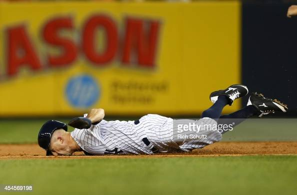 Brett Gardner the New York Yankees dives into second base on the back end of an attempted double during the first inning in a MLB baseball game at...