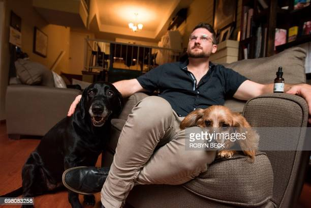 Brett Hartman discusses the use of cannabis to treat aliments in animals as he sits with his dogs Cayley a sixyearoldLabrador Retriever and Brutus a...