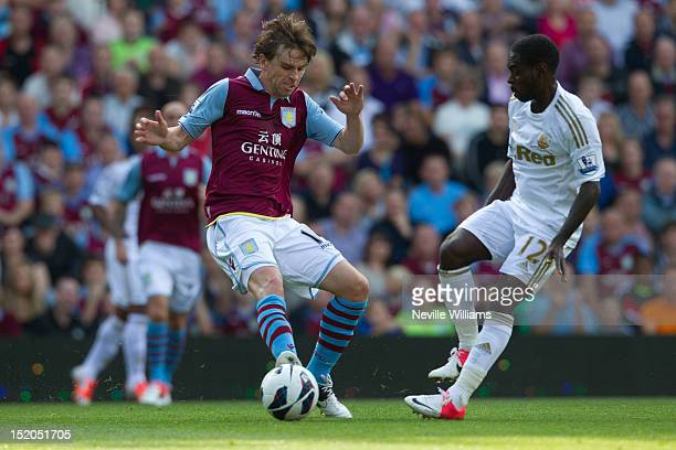 Brett Holman of Aston Villa is challenged by Nathan Dyer of Swansea City during the Barclays Premier League match between Aston Villa and Swansea...