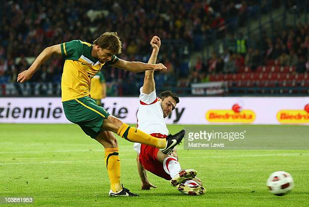 Brett Holman of Australia beats Michal Wojtkowiak of Poland to score a goal during the International Friendly match between Poland and Australia at...