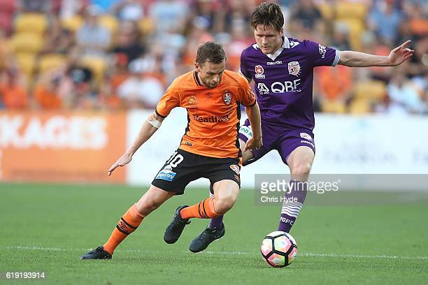 Brett Holman of the Roar and Alexander Grant of the Glory compete for the ball during the round four ALeague match between the Brisbane Roar and...