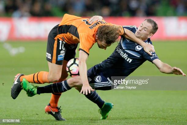 Brett Holman of the Roar and Leigh Broxham of the Victory compete for the ball during the ALeague Semi Final match between Melbourne Victory and the...