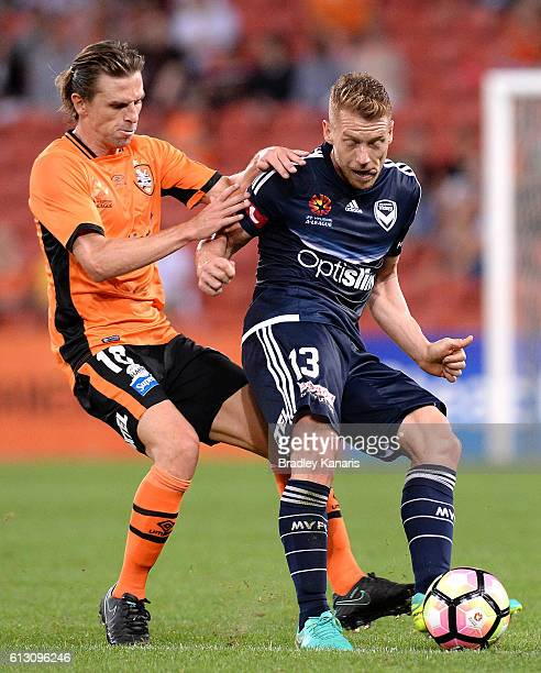 Brett Holman of the Roar and Oliver Bozanic of the Victory compete for the ball during the round one ALeague match between the Brisbane Roar and...