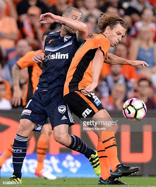 Brett Holman of the Roar is challenged by the defence during the round one ALeague match between the Brisbane Roar and Melbourne Victory at Suncorp...