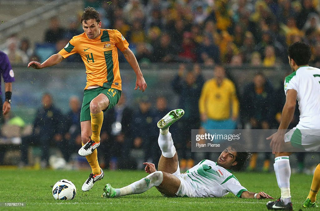 Brett Holman of the Socceroos is tackled by Ahmad Ibrahim of Iraq during the FIFA 2014 World Cup Asian Qualifier match between the Australian...
