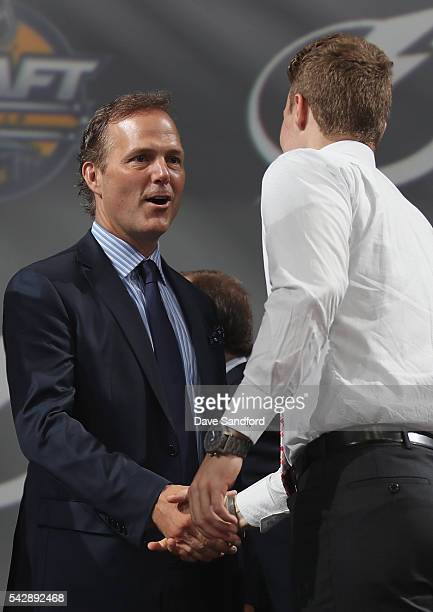 Brett Howden shakes hands with head coach John Cooper after being selected 27th overall by the Tampa Bay Lightning during round one of the 2016 NHL...