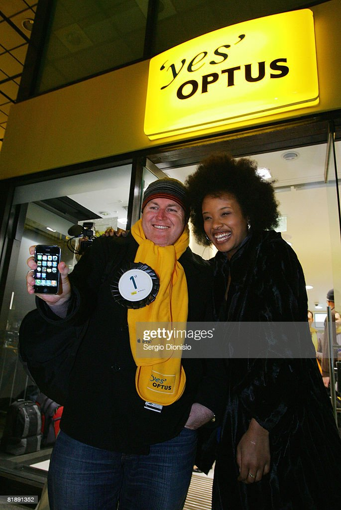 Brett Howell (L) the first to purchase the new Apple iPhone in Australia, poses with Television presenter Faustina 'Fuzzy' Agolley at the George Street Optus Store on July 11, 2008 in Sydney, Australia. The iPhone 3G is a multimedia mobile device with a touch screen that enables email and web browsing.