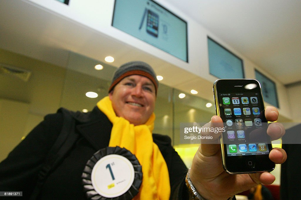 Brett Howell, the first to purchase the new Apple iPhone in Australia, poses with his handset at the George Street Optus Store on July 11, 2008 in Sydney, Australia. The iPhone 3G is a multimedia mobile device with a touch screen that enables email and web browsing.