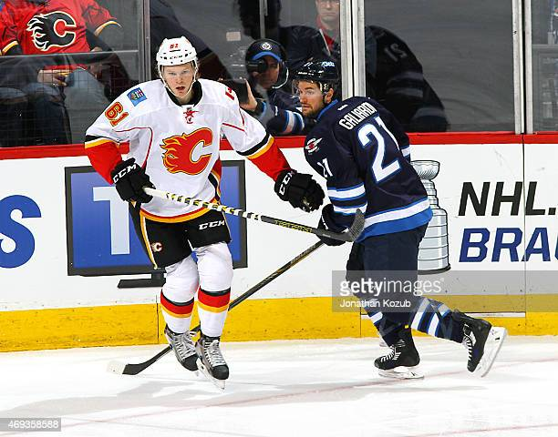Brett Kulak of the Calgary Flames and TJ Galiardi of the Winnipeg Jets follow the play during second period action on April 11 2015 at the MTS Centre...