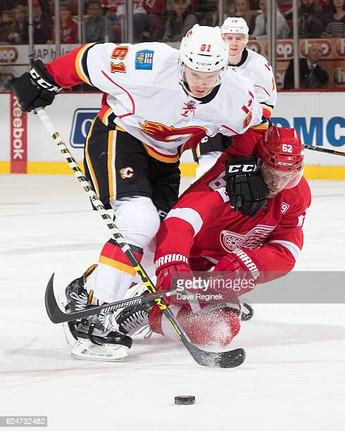 Brett Kulak of the Calgary Flames battles for the puck with Thomas Vanek of the Detroit Red Wings during an NHL game at Joe Louis Arena on November...